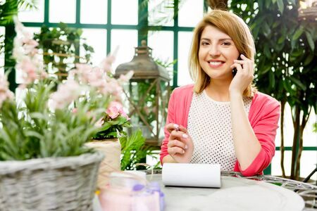 Happy flower seller with phone in flower shop Stock Photo