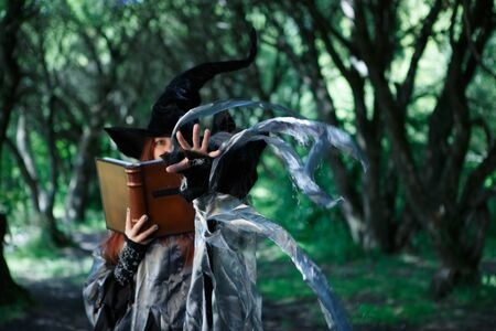 Photo of witch with magic book Stock Photo