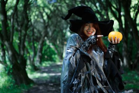 Photo of witch pointing finger at pumpkin