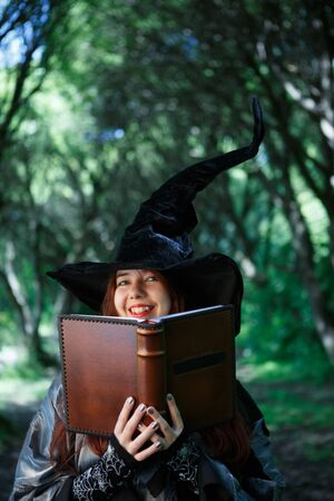 Image of smiling witch with magic book Stock Photo