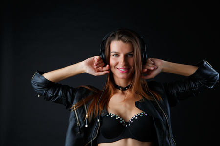 Studio image of young woman in headphones with hands at her head