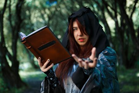 Witch with spellbook in hood