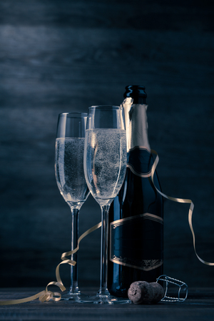 Toned photo of two wine glasses with sparkling champagne, bottle, cork