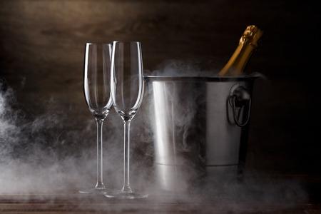Foto van twee wijnglazen, ijzeremmer met fles, stoom Stockfoto