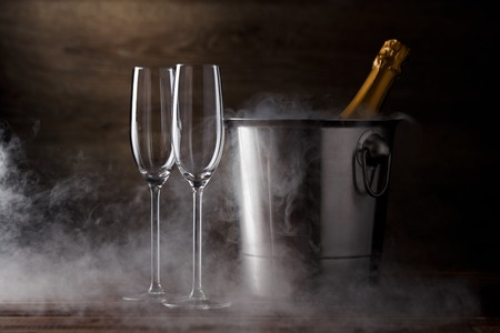 Photo of two wineglasses, iron bucket with bottle, steam