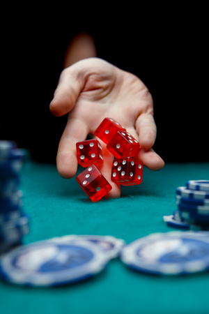 Image of man throwing red dices on table with chips in casino