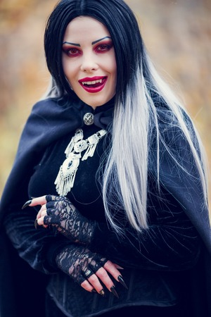 Photo of licking vampire woman with long hair, red eyes