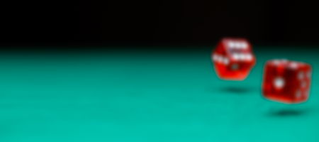 Defocused photo of two dice falling on green table Stock Photo