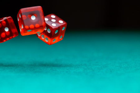 Picture of several red dice falling on green table,, empty space for text