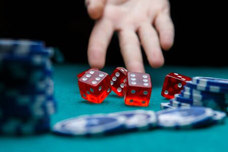 Picture of man throwing dice on table with chips in casino