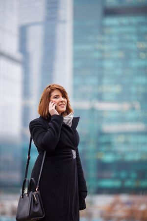 Photo of woman in black coat talking on phone