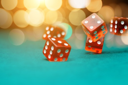 Image of abandoned red dices on green table
