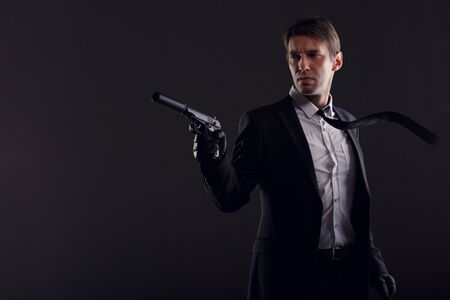 Portrait of man in leather gloves with gun isolated on black background.