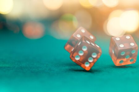 Photo of several red dice falling on green table in casino