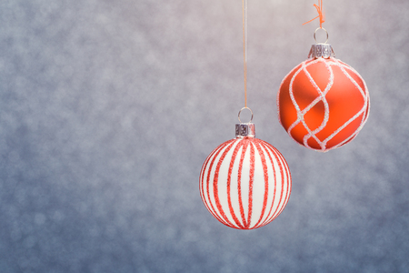 Photo of red Christmas tree with pattern of balls on gray blurred background.