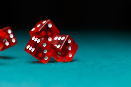 Photo of several red dice falling on green table Stock Photo