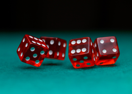 Picture of several red dice falling on green table on black background Stock Photo