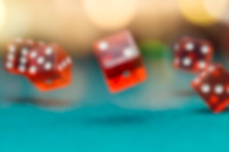 Image of several red dice falling on green table in casino Stock Photo