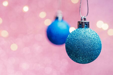 Image of two Christmas blue balls on pink background with spots.