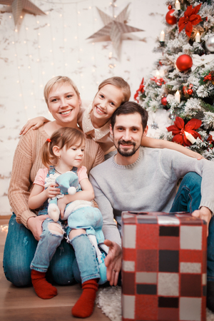 New Years photo of parents with daughters on background of decorated pine Standard-Bild