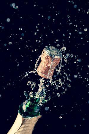 Eröffnung Flasche Champagner auf leeren schwarzen Hintergrund