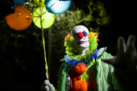 Photo of clown with colorful balloons