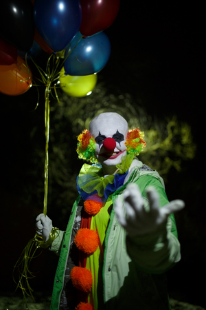 Photo of smiling clown with colorful balloons at night in street Stock Photo