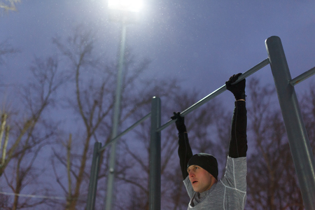 Athlete pulling on bar in evening Stock Photo