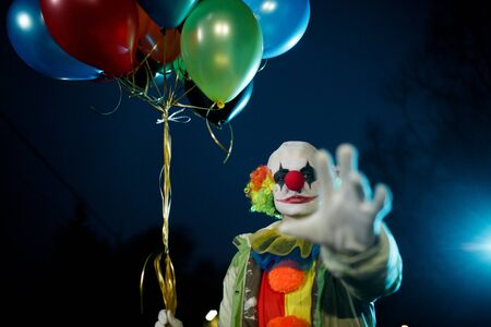 Image of clown with balls in hands at night on street Stock Photo