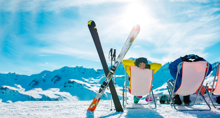 Image from back of vacationers in armchair, skis, sticks in snowy resort Stok Fotoğraf - 95910499