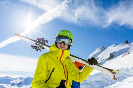 Photo of sports man wearing helmet and mask, with skis on his shoulder Archivio Fotografico