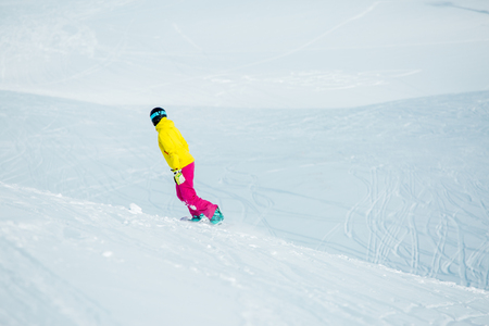 Picture from back of girl in sports clothes snowboarding Stock Photo