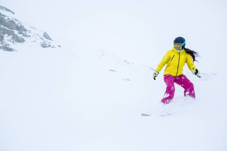 Photo of female athlete wearing helmet with developing hair, snowboarding from mountain slope