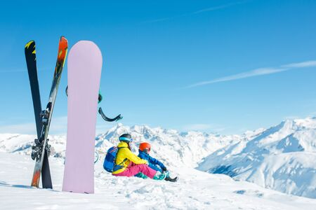Image of snowboard, ski on background of sitting sports couple on snowy hill in winter afternoon Stock Photo