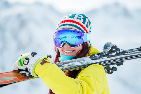 Portrait of woman in mask with skis on her shoulder standing sideways 版權商用圖片