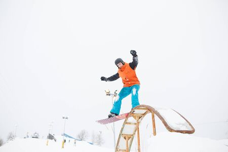 Image of young sportive man skiing on snowboard with springboard against snowy sky Banque d'images