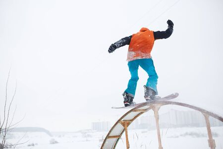 Picture from back of athlete skating on snowboard with springboard