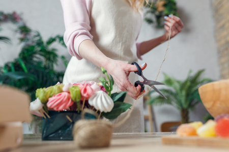 Photo of florist with scissor-cutting rope at table with bouquet, marmalade, marshmallow in room Foto de archivo - 98447383