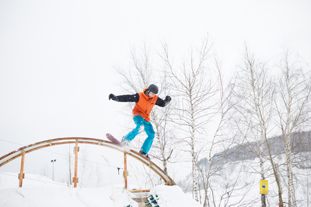 Image of athlete skating on snowboard from springboard against background of trees
