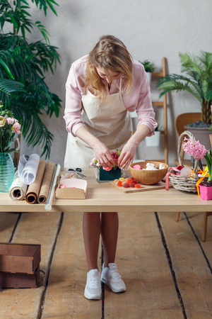 Picture of florist woman in apron with marshmallow, marmalade at table Foto de archivo - 99004402