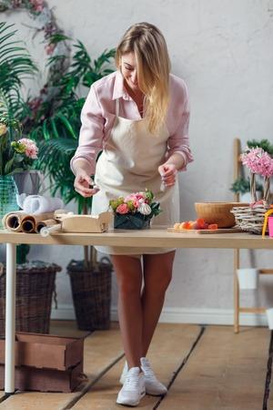 Picture of blonde florist making bouquet of marshmallows, flowers Foto de archivo - 99004888