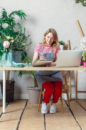 Photo of florist woman with notebook at table with laptop