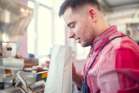 Image of man sniffing coffee in paper bag Stock Photo