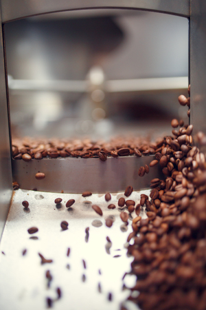 Picture of falling roasted coffee beans from roaster Imagens