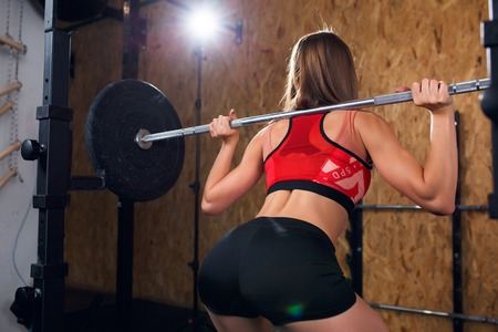 Photo from back of sports woman crouching with bar Stock Photo