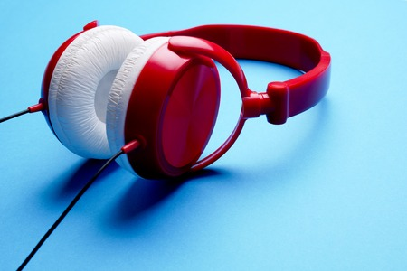 Photo of red with white headphones close-up on empty blue background Stock Photo