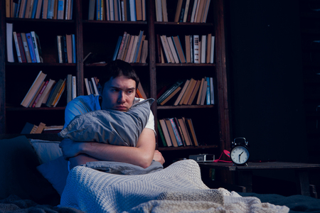 Photo of man with insomnia sitting in bed next to alarm clock