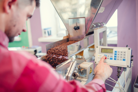Image of young businessman weighing coffee grains on scales