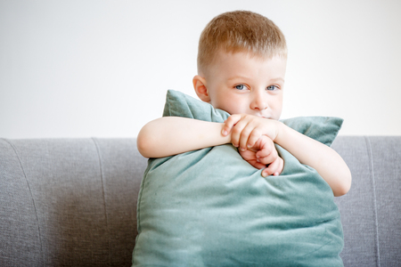Picture of boy with pillow sitting on couch