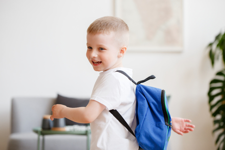 Image of boy with backpack near sofa